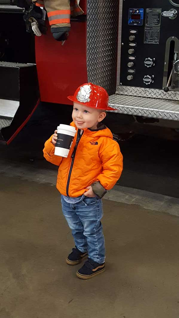 Young boy happy holding a drink in front of the fire truck
