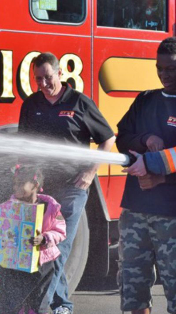 Young happy girl with firefighters